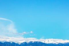 Picchi e cielo blu di montagne con il fondo delle nuvole Immagini Stock