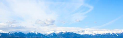 Picchi e cielo blu di montagne con il fondo delle nuvole Fotografie Stock Libere da Diritti