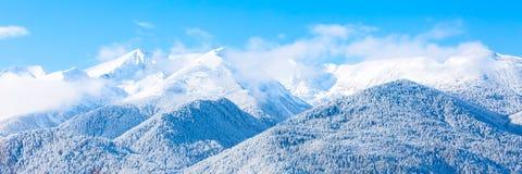 Picchi e cielo blu di montagne con il fondo delle nuvole Immagini Stock Libere da Diritti