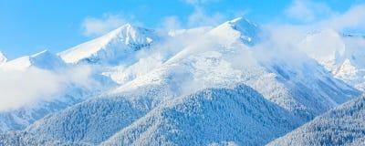 Picchi e cielo blu di montagne con il fondo delle nuvole Immagine Stock Libera da Diritti