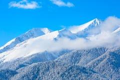 Picchi e cielo blu di montagne con il fondo delle nuvole Fotografia Stock