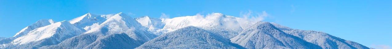 Picchi e cielo blu di montagne con il fondo delle nuvole Fotografie Stock