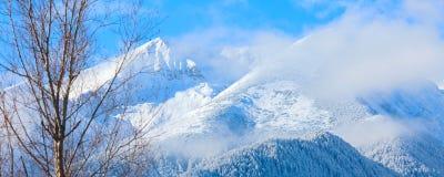 Picchi e cielo blu di montagne con il fondo delle nuvole Immagine Stock