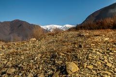 Picchi innevati ad alto paesaggio con la priorità alta a terra della pietra secca Fotografia Stock