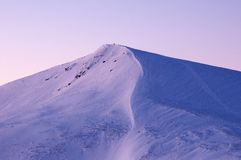 Picchi innevati delle montagne nei raggi dell'alba nella mattina gelida di inverno immagine stock libera da diritti