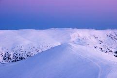 Picchi innevati delle montagne nei raggi dell'alba nella mattina gelida di inverno fotografia stock