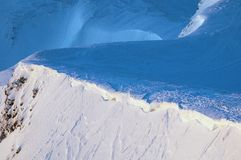 Picchi innevati delle montagne nei raggi dell'alba nella mattina gelida di inverno fotografia stock libera da diritti