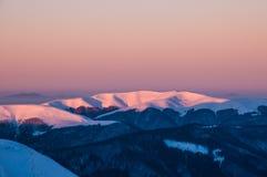 Picchi innevati delle montagne nei raggi dell'alba nella mattina gelida di inverno fotografie stock libere da diritti