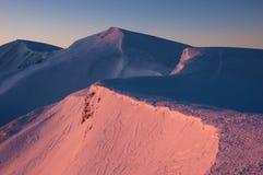Picchi innevati delle montagne nei raggi dell'alba nella mattina gelida di inverno immagini stock libere da diritti