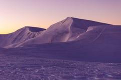 Picchi innevati delle montagne nei raggi dell'alba nella mattina gelida di inverno immagini stock