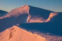 Picchi innevati delle montagne nei raggi dell'alba nella mattina gelida di inverno immagine stock