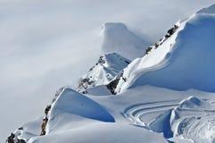 Picchi innevati distanti sopra le nuvole Fotografia Stock