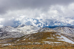 Picchi innevati ed erba gialla sotto le nuvole Alpe australiana Immagine Stock