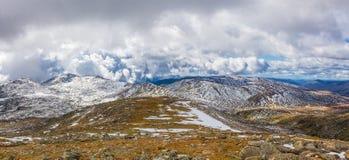 Picchi innevati ed erba gialla sotto le nuvole Alpe australiana Immagini Stock Libere da Diritti