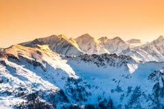 Picchi nevosi di inverno delle alpi Panorama della montagna illuminato dal tramonto a tempo di sera L'Austria e la Svizzera, Euro Immagine Stock