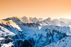 Picchi nevosi di inverno delle alpi Panorama della montagna illuminato dal tramonto a tempo di sera L'Austria e la Svizzera, Euro Fotografia Stock Libera da Diritti