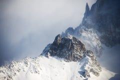 Picchi rocciosi coperti di neve in un tempo nebbioso Fotografia Stock