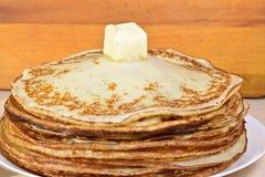 Picchiettio di burro di fusione su un mucchio dei pancake immagini stock