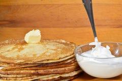 Picchiettio di burro di fusione su un mucchio dei pancake fotografia stock