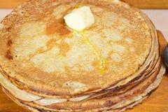 Picchiettio di burro di fusione su un mucchio dei pancake immagini stock libere da diritti