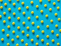Picchiettio giallo della pallina da tennis sul blu fotografia stock