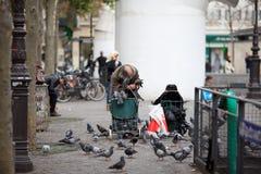 piccioni d'alimentazione dell'indigente nella via Fotografie Stock