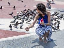 Piccioni d'alimentazione della bella giovane donna a Barcellona, Spagna Fotografia Stock