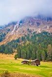 Picco alpino nella vista di verticale della capanna della montagna e della nebbia Fotografia Stock