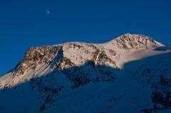 Picco della montagna nevosa al sole Fotografie Stock