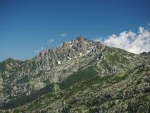 Picco di alta montagna di estate con cielo blu e le nuvole Fotografia Stock