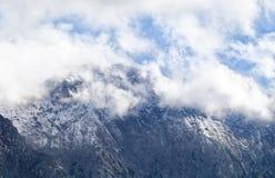 Picco di alta montagna in nuvole bianche Fotografia Stock