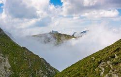 Picco di alta montagna in nuvole fra le colline Immagine Stock Libera da Diritti