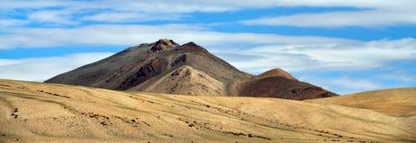 Picco di alta montagna in tonalità marroni, illuminate dal sole, cielo blu con le bande delle nuvole bianche, viaggio attraverso  Immagini Stock
