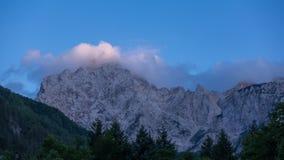 Picco di montagna alpino nel tramonto su cielo blu, sulle nuvole e sulla foresta in priorità alta Immagini Stock Libere da Diritti