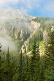 Picco di montagna attraverso le nubi Wispy immagini stock libere da diritti