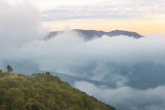Picco di montagna che compare sopra le nuvole immagine stock libera da diritti