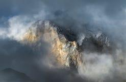 Picco di montagna che dà una occhiata attraverso le nuvole in montagne di Caucaso immagini stock