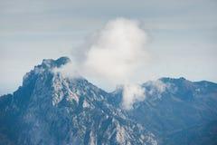 Picco di montagna con le nuvole in alpi austriache Fotografia Stock