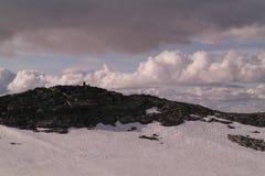 Picco di montagna con un cairn di pietra Fotografia Stock