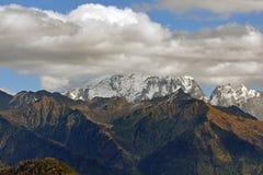 Picco di montagna della neve di Haba in nuvole Fotografia Stock