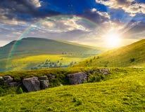 Picco di montagna dietro il pendio di collina con i massi al tramonto Fotografia Stock