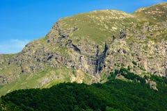 Picco di montagna rocciosa con la cascata Immagine Stock Libera da Diritti