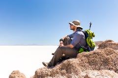 Picco di montagna di seduta di viaggiatore con zaino e sacco a pelo turistico, sopra il deserto del sale, Bol Immagine Stock
