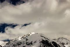 Picco di montagna sotto la copertura delle nuvole e della neve Fotografie Stock Libere da Diritti
