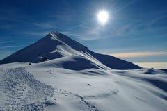 Picco di Snowy in alpi italiane con la gente che scala la cresta Immagini Stock Libere da Diritti
