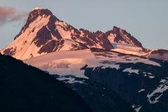 Picco innevato nella catena montuosa della costa, Columbia Britannica, Canada durante il tramonto Fotografia Stock