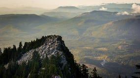 Picco roccioso davanti alle foreste ed alle colline immagini stock libere da diritti