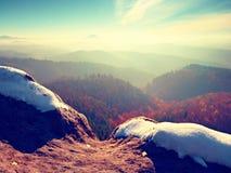 Picco roccioso sopra il freddo inverso in montagne, nebbia variopinta di inverno della foschia Valle nebbiosa Immagine Stock