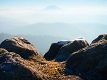 Picco roccioso sopra il freddo inverso in montagne, nebbia variopinta di inverno della foschia Valle nebbiosa Fotografia Stock