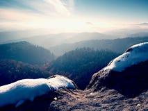 Picco roccioso sopra il freddo inverso in montagne, nebbia variopinta di inverno della foschia Valle nebbiosa Fotografia Stock Libera da Diritti
